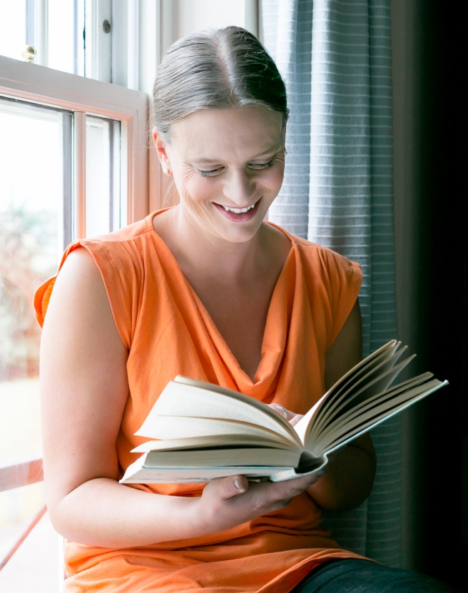 Smiling author sitting on a window sill reading a book